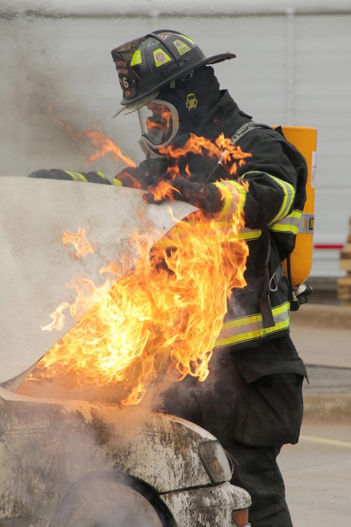 A firefighter checks under the hood of a burning car at CITA Kirkwoods fire school on Sept. 21.