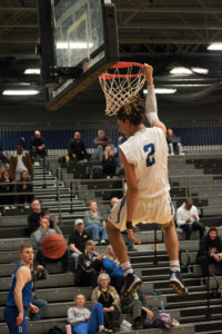 2 Seybian Sims hangs from the rim after a slam dunk while playing against Des Monies Area Community College (DMACC) on Feb. 12.