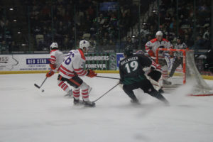Photo of Roughriders forward, # 19 Tyler Rollwagen, battles with the oppostion for the puck during the Kirkwood student night game on Jan. 31.