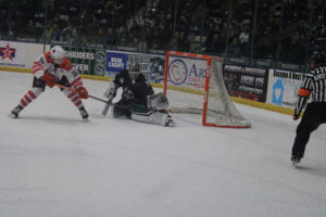 Photo of Roughriders goalkeeper, #35 Derek Mullahy, deflects the puck from an opposing player during Kirkwood student night Jan 31.