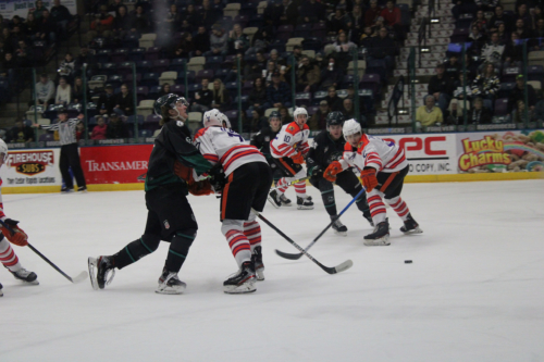 Photo of Roughriders forward, #8 Michael Posma, skating into an opposing player during college night Jan 31.