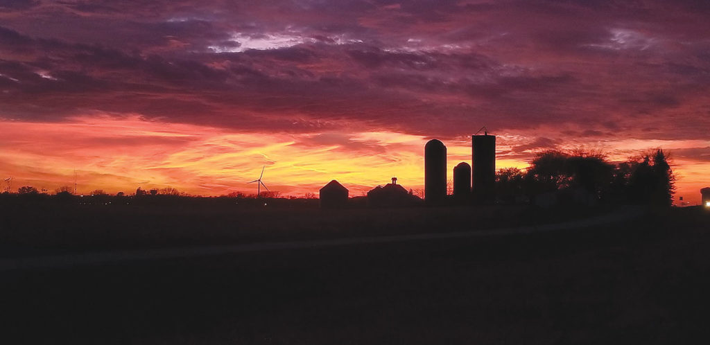 Photo of sunset behind farm with silos and a wind turbine visible